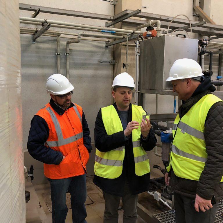 El Director General de Cambio Climático con el vaso de agua transparente tras la depuración de lixiviados